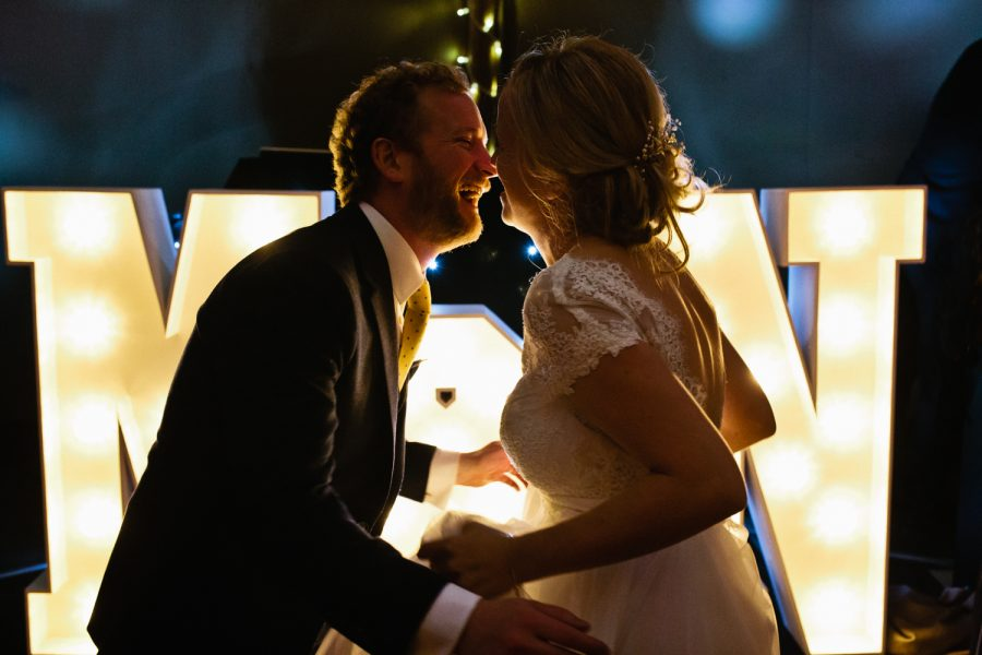 a bride and groom dance under large letter light ata tipi wedding in kent Kent Documentary wedding Photography