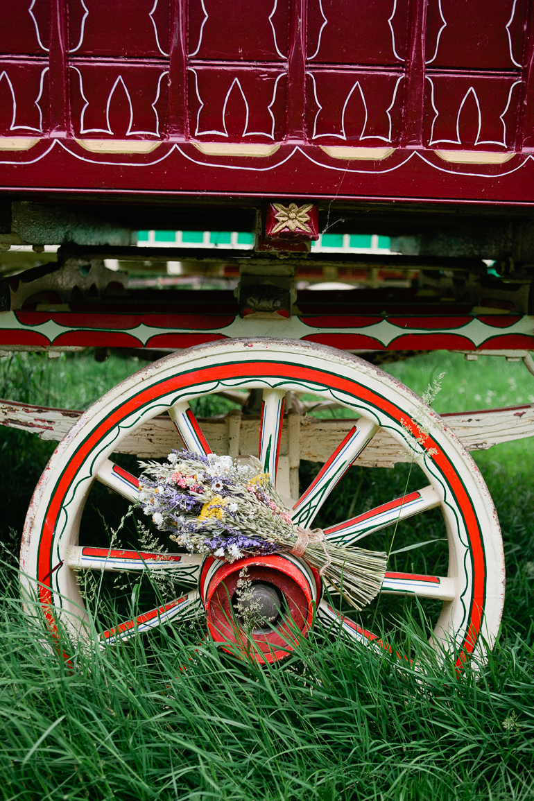 A dried wild flower bouquet from Artisan Dried Flower Co rests on a gypsey caravan wheel at south farm wedding venue