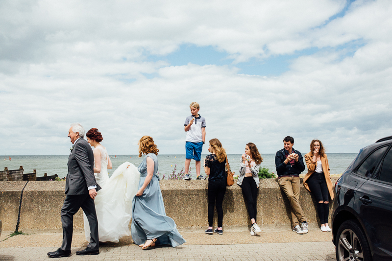 A bride and bridal party walk to the East Quay wedding venue form the Hotel Continental in Whitstable Kent