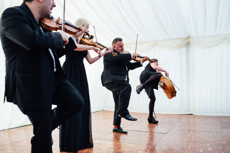 A string quartet playing music at a Great Higham Barn wedding in Kent - wedding photography Kent