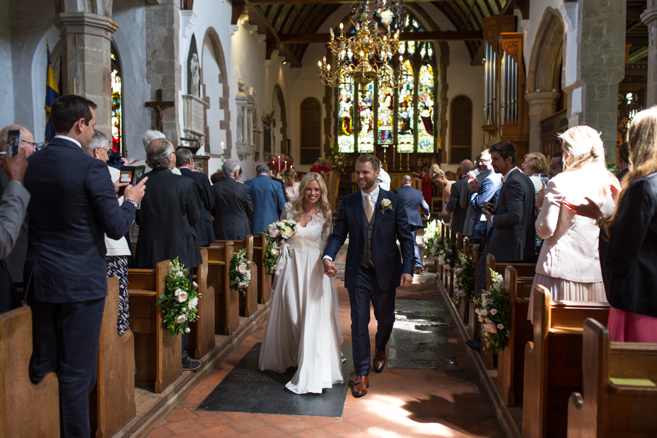 A bride and groom walk back down the aisle at their Wedding ceremony at Mayfield Church