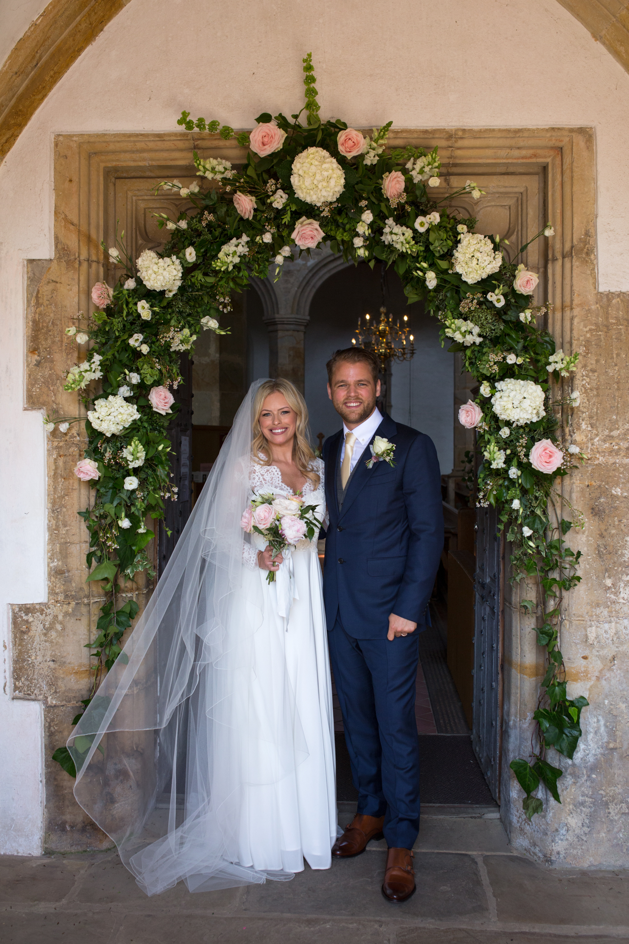 A portrait of a bRide and groom outside Mayfield Church in Kent