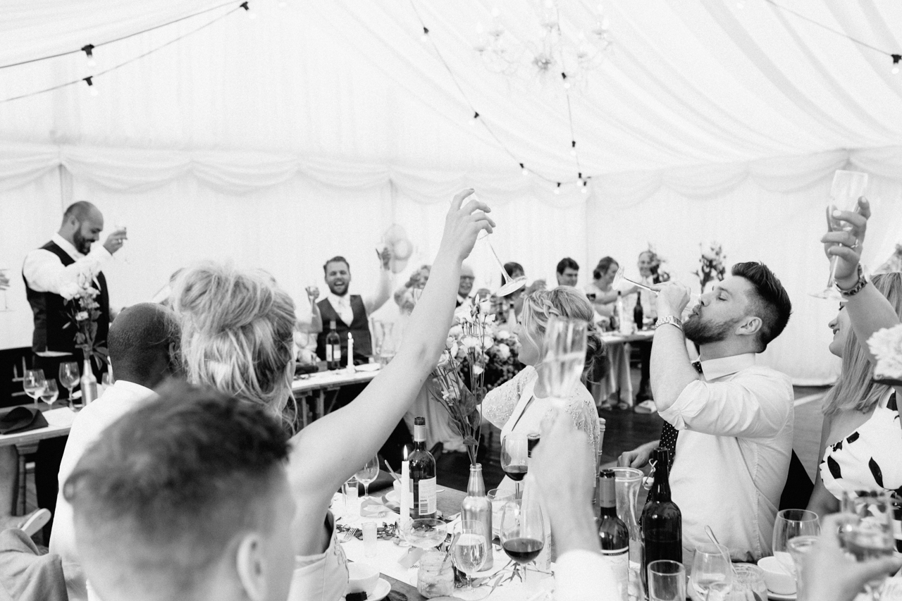 A black and white photography of wedding speeches in the marquee at Sprivers Mansion