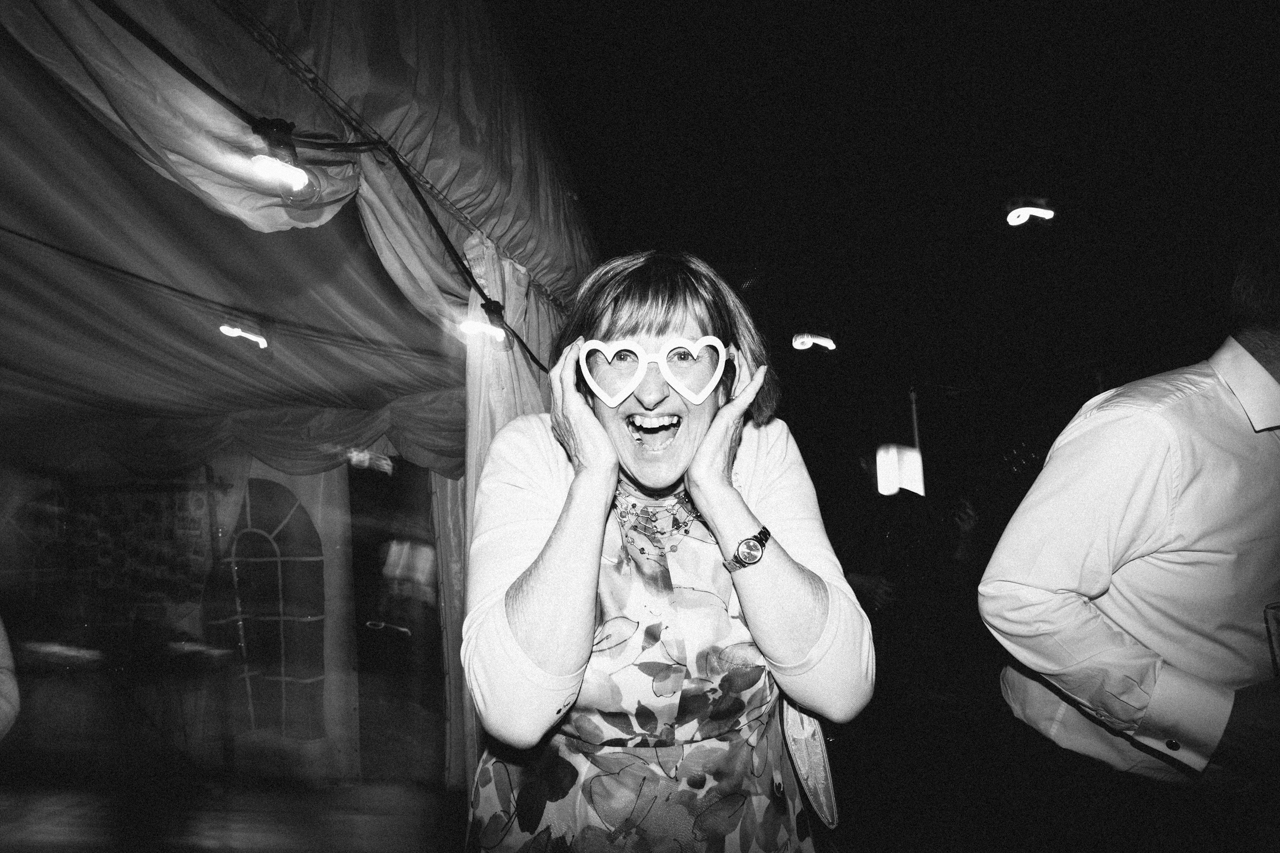 Humourous black and white photography of a wedding guest wearing heart glasses , Kent documentary wedding photography