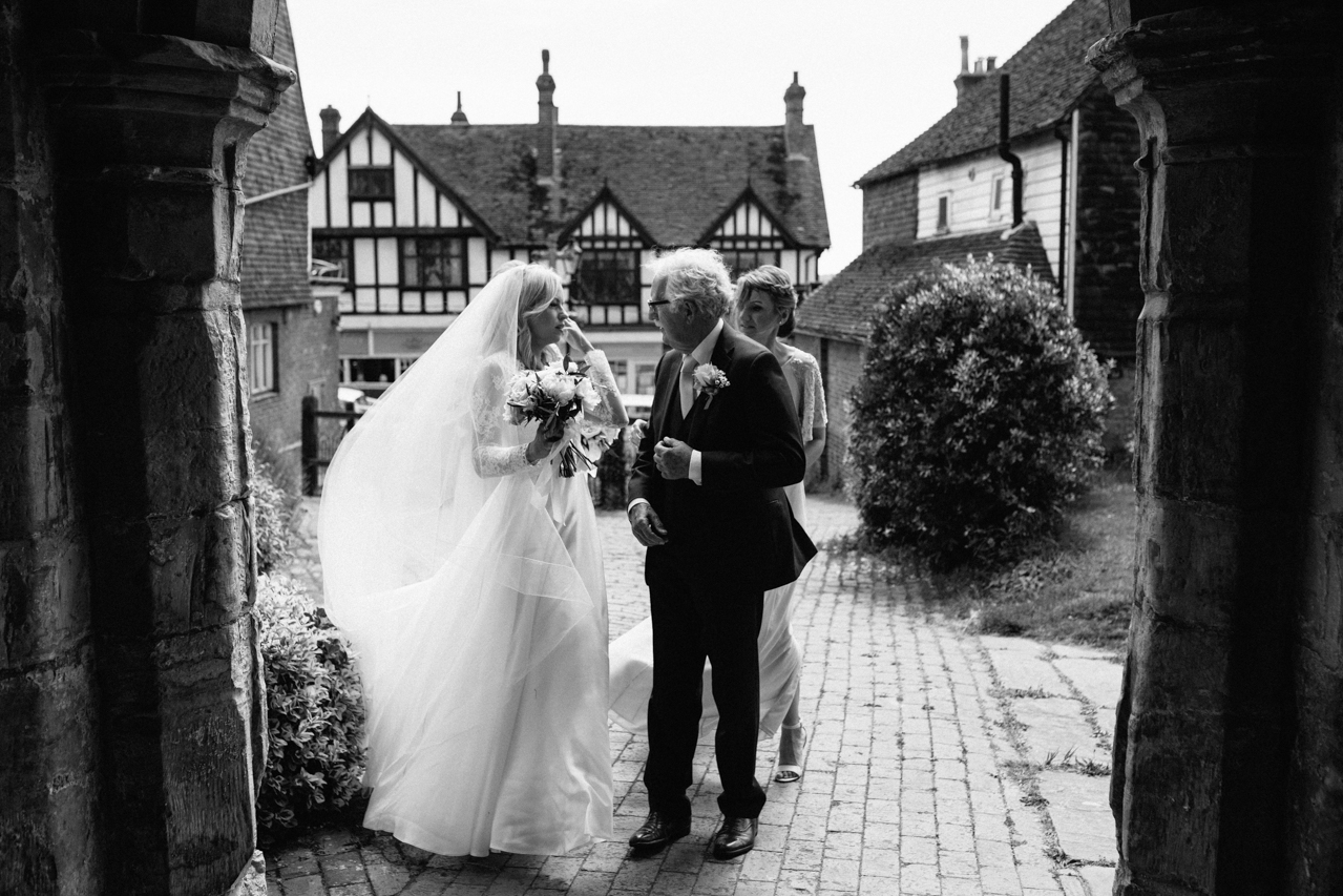 A black and white photography of a bride and her father outside of Mayfiled Church just before a weddign ceremony