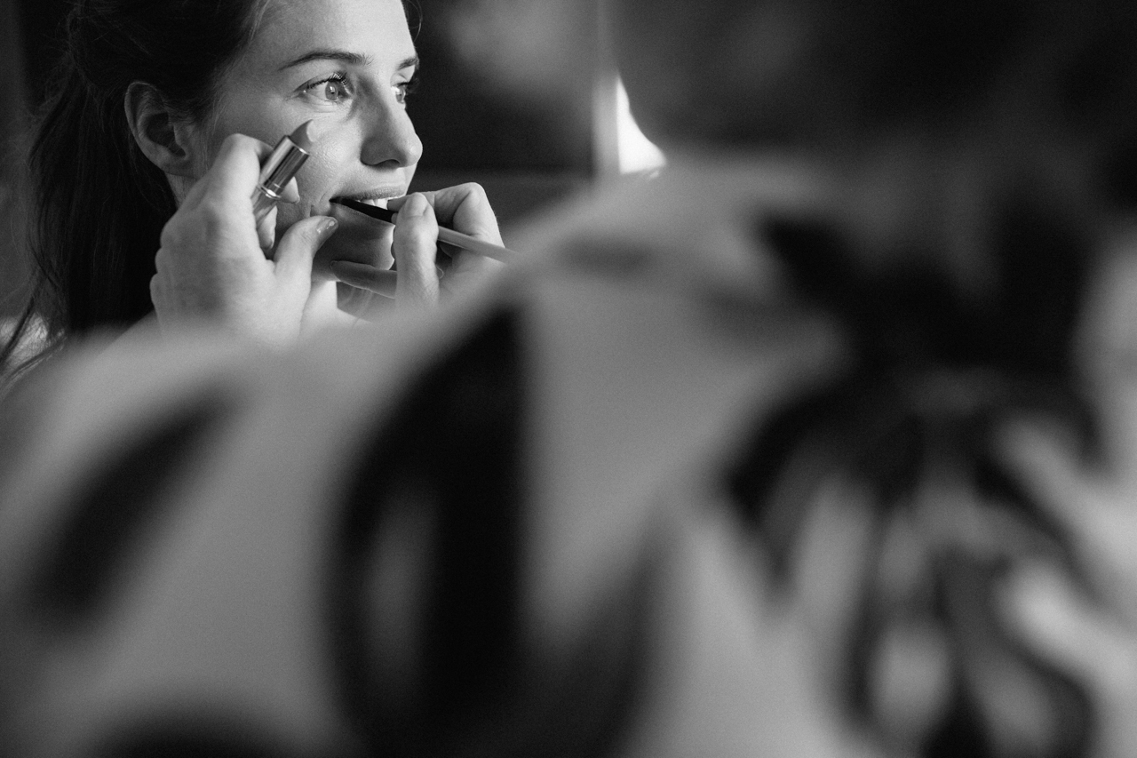 A black and white candid photo of a bride getting ready