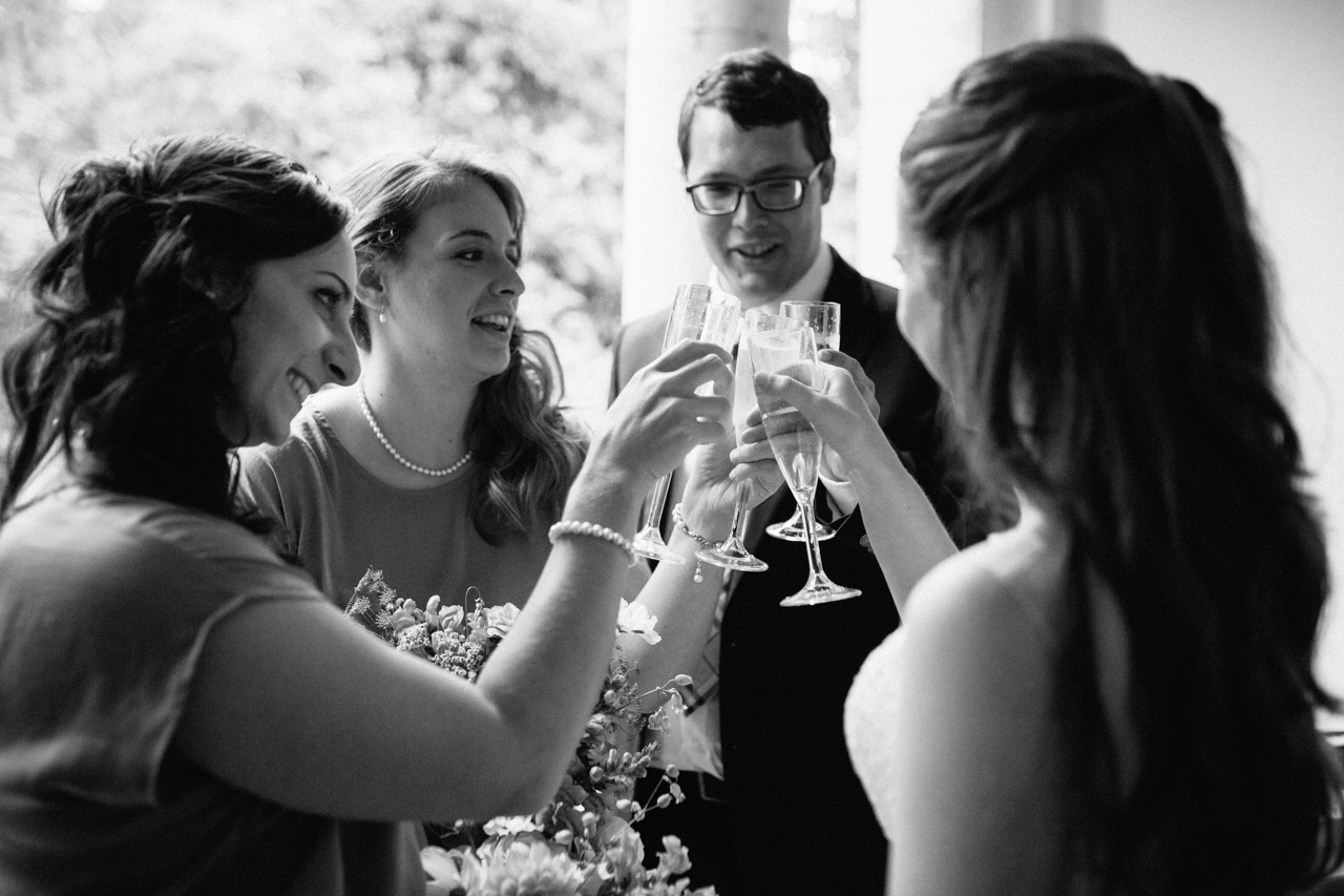 A black and white photograph of guest clinking glasses at a wedding reception at The Hill Top Gardens and Pergola Wedding on Londons Hampstead Heath - Kent documentary wedding photography