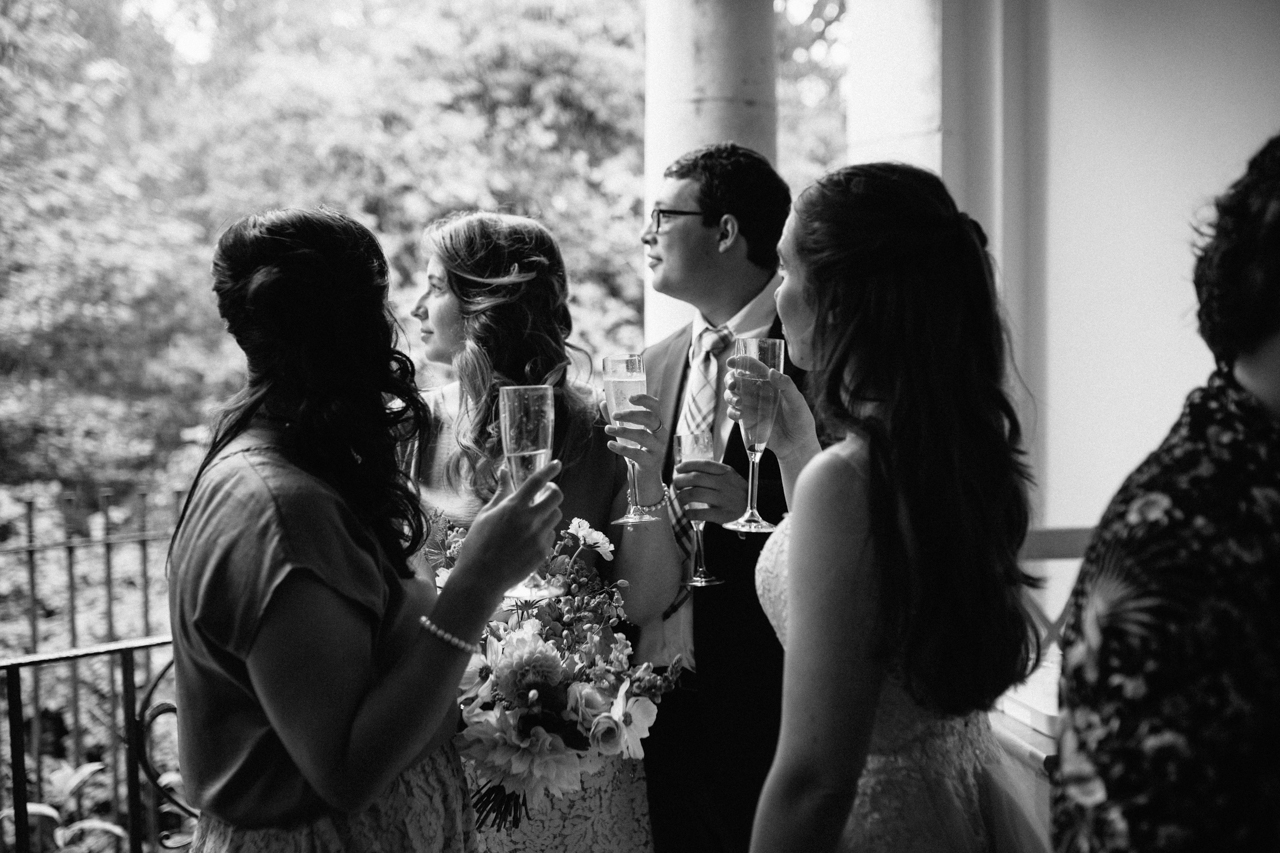 A black and white photograph of guests looking out at the rain during a wedding reception at The Hill Top Gardens and Pergola Wedding on Londons Hampstead Heath - Kent documentary wedding photography