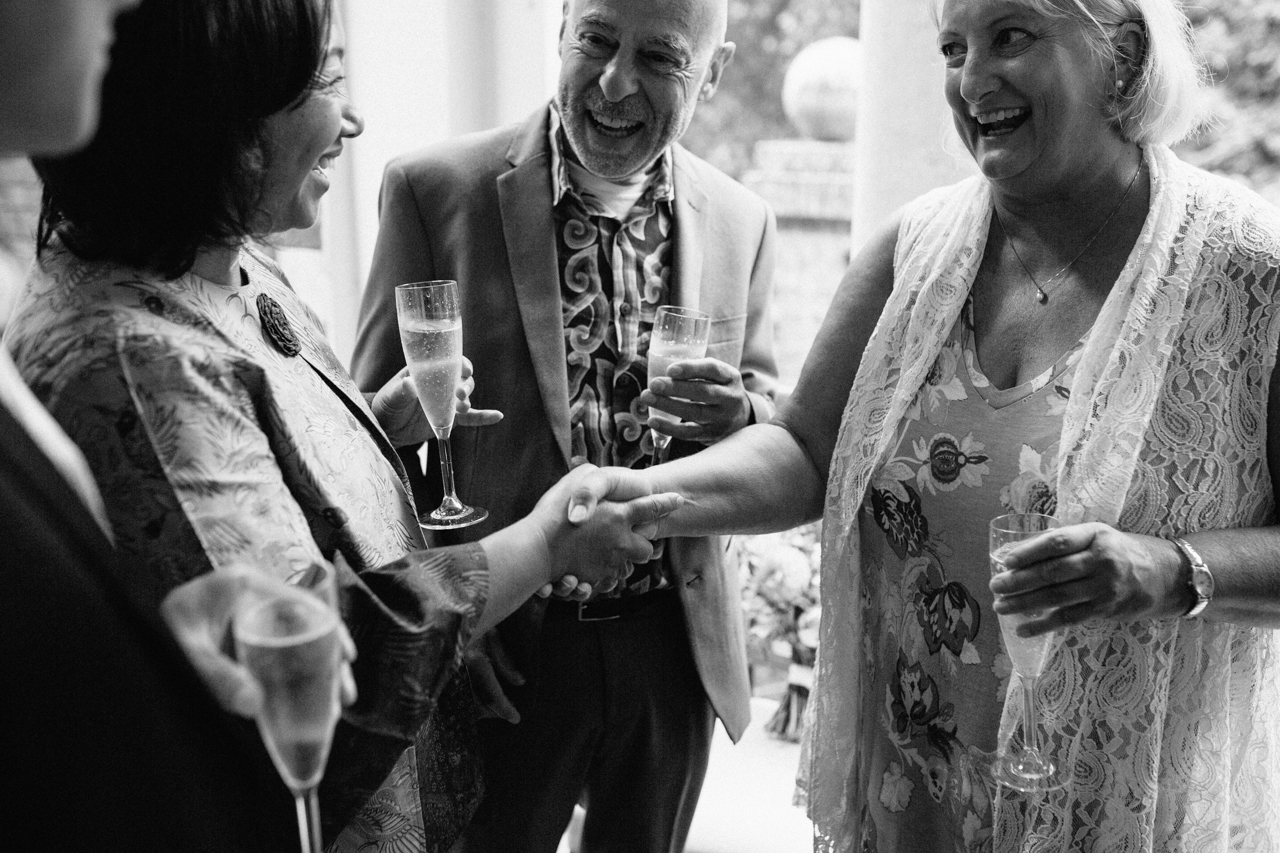 A black and white photograph of guests shacking hands at a wedding reception at The Hill Top Gardens and Pergola Wedding on Londons Hampstead Heath - Kent documentary wedding photography