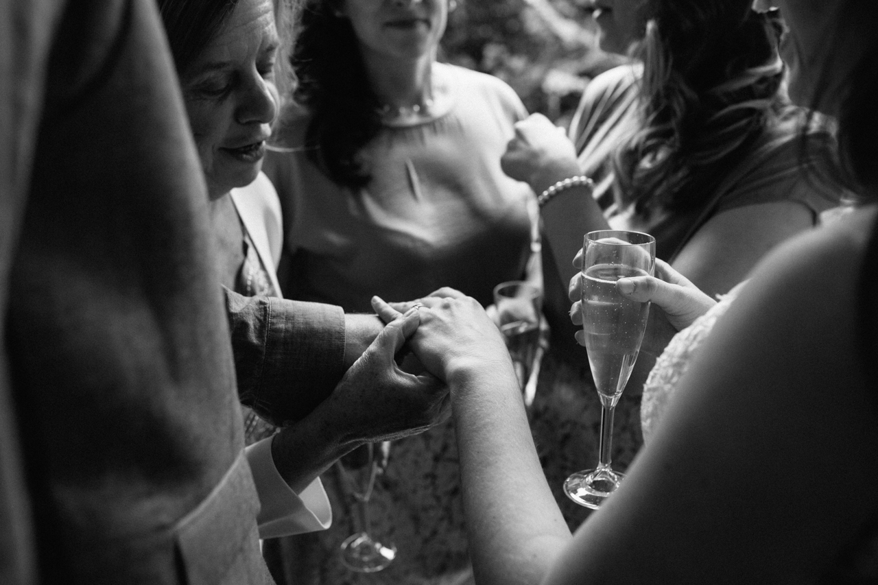 A black and white photograph of guests admiring the brides wedding ring at a wedding reception at The Hill Top Gardens and Pergola Wedding on Londons Hampstead Heath - Kent documentary wedding photography