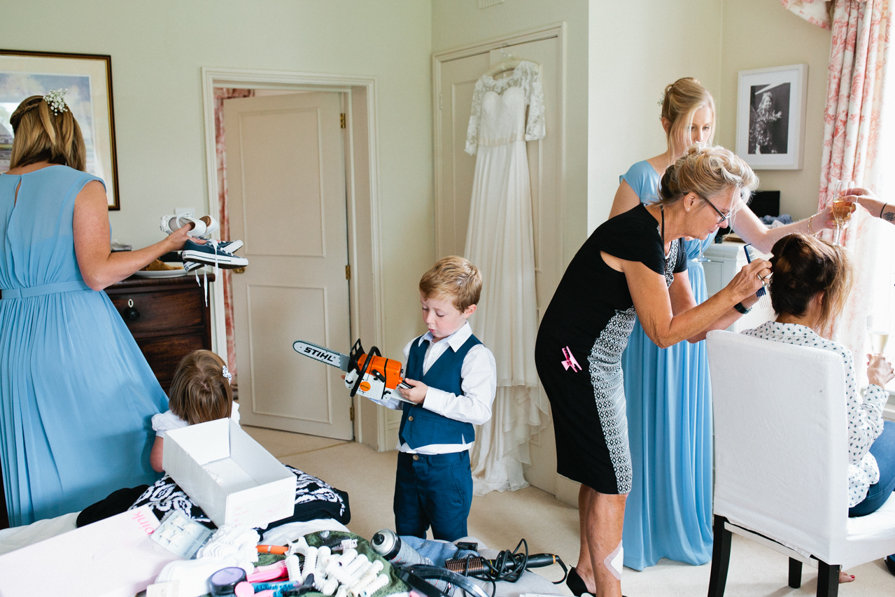 Humorous colour photography of a page boy during bridal preparations before a wedding at Englefield Estate – Kent Documentary wedding photography