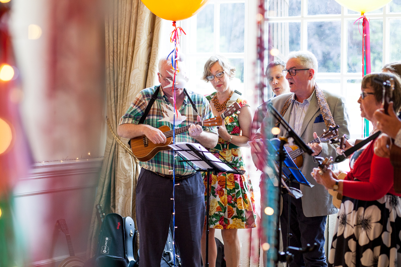 Colour photography of a ukulele band playing at a wedding at West Heath School in Sevenoaks | Kent Documentary wedding photography