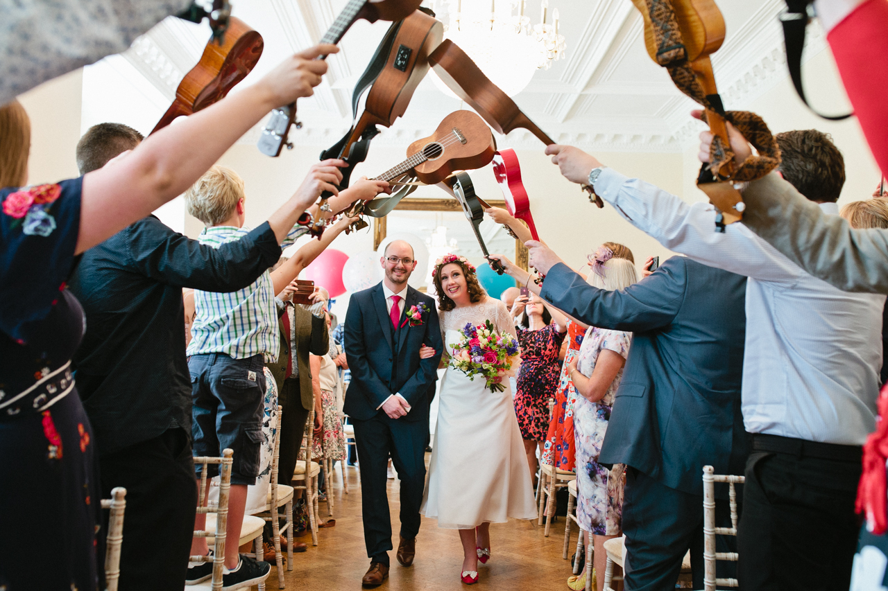 Colour photography of a ukulele band forming an archway for a bride and groom to walk under at a Wes Anderson Themed wedding | West Heath School in Sevenoaks | Kent Documentary wedding photography