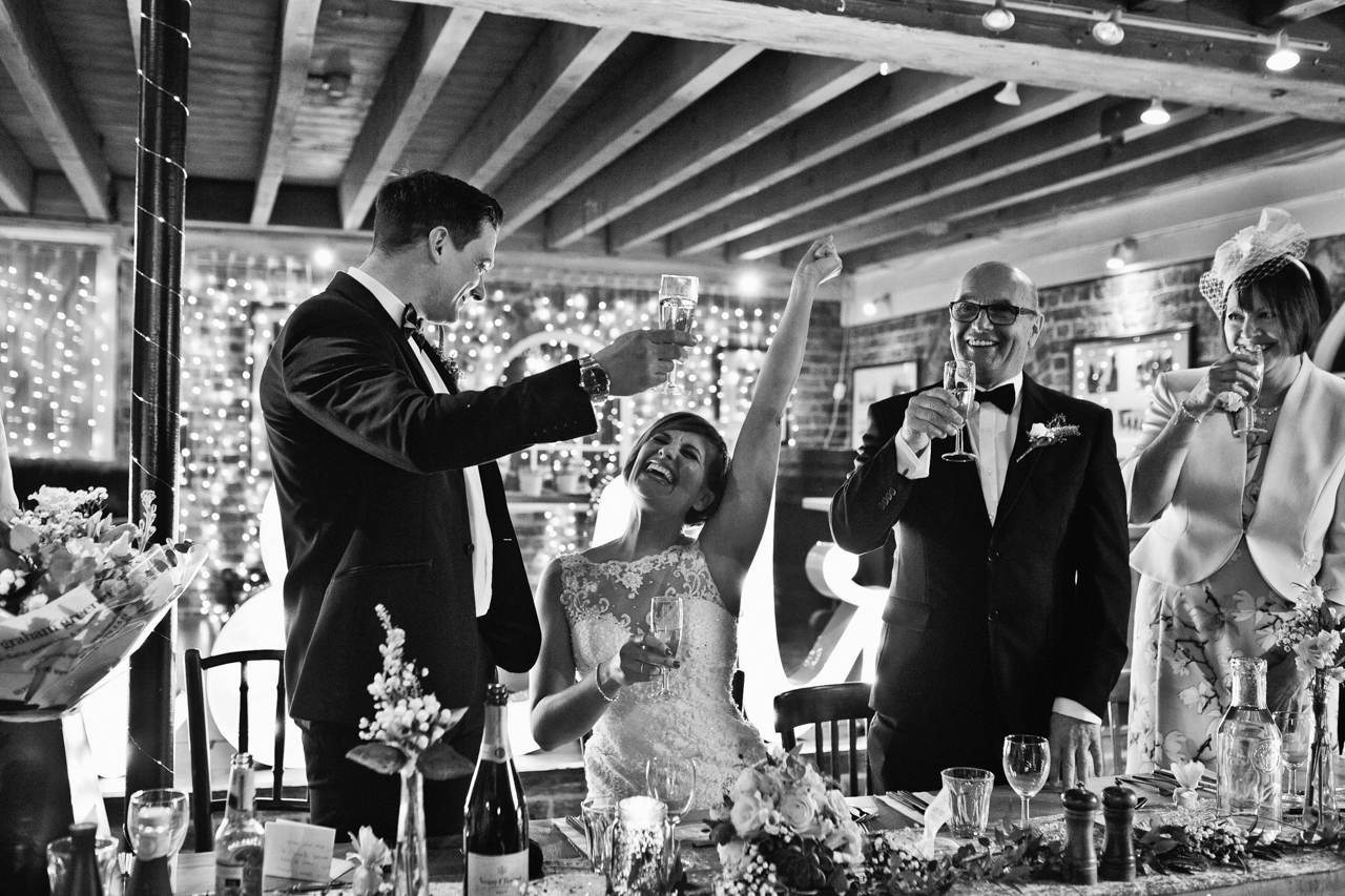 A black and white photography of a toast at a winter wedding at the East Quay Wedding Venue
