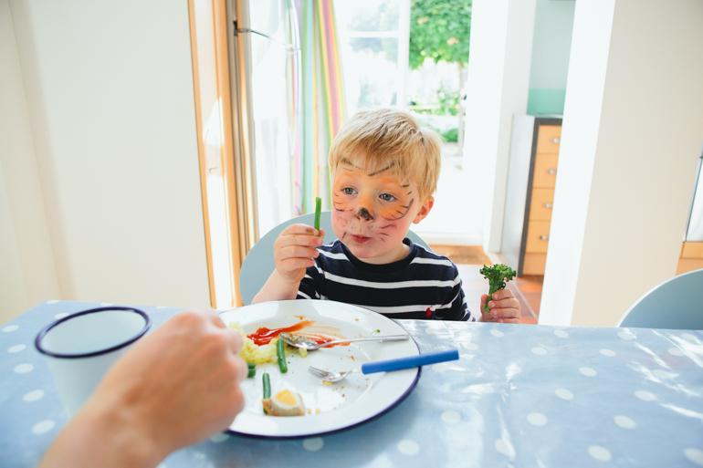 Little boy eats his vegatable at an informal family portrait session in Kent