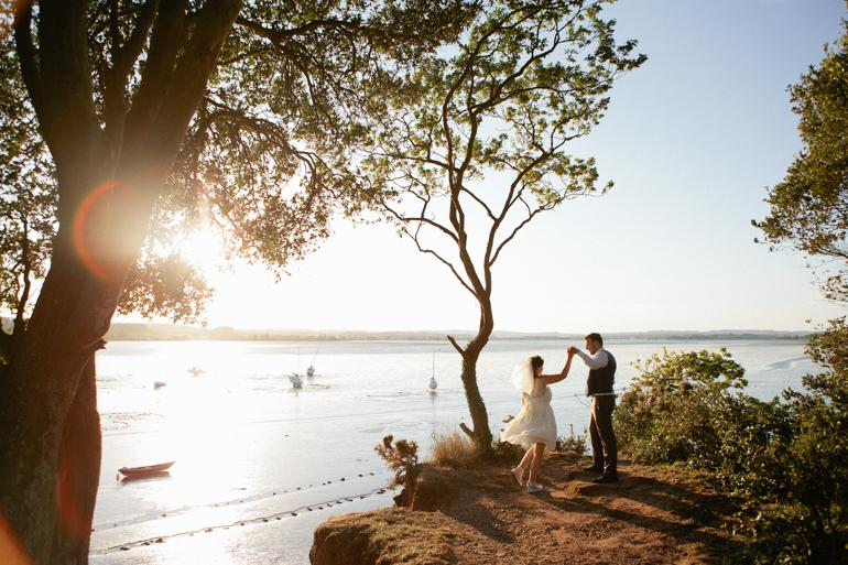A bride and groom dance in the late evening sunlight on the cliffs at their quirky DIY wedding in Lympstone village hall, near Exeter Devon.