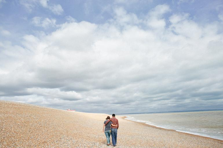 A young engaged couple walk off into the distance on the shingle beach Young engaged couple embracing and kissing under a fishing boat at their Dungeness engagement shoot