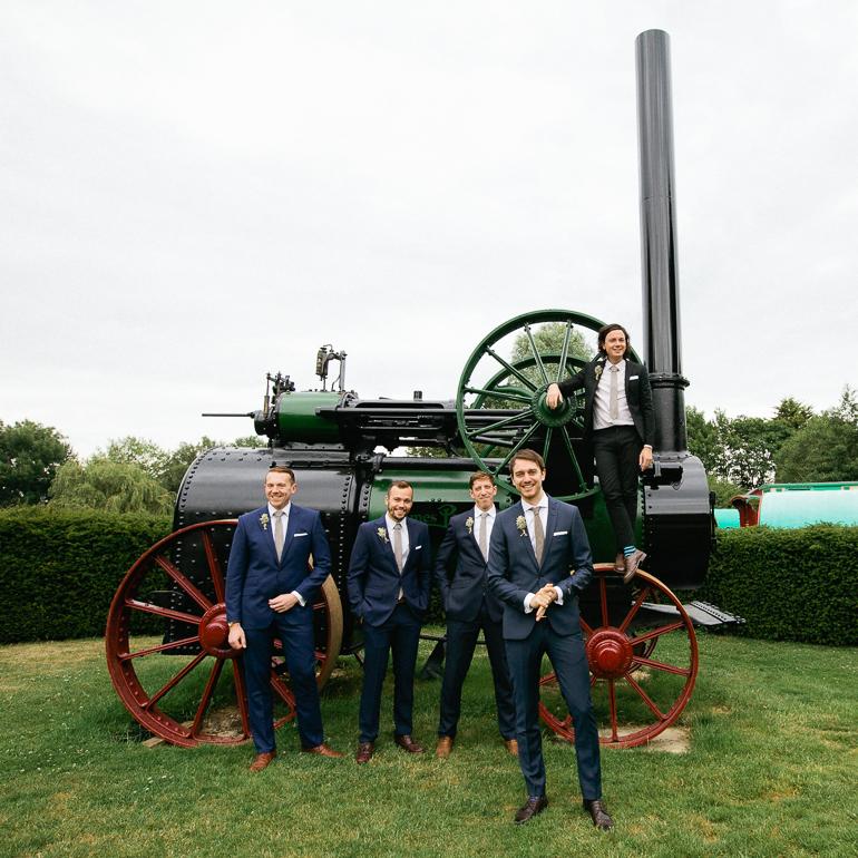 Groom and grooms men posing on a vintage steam engine
