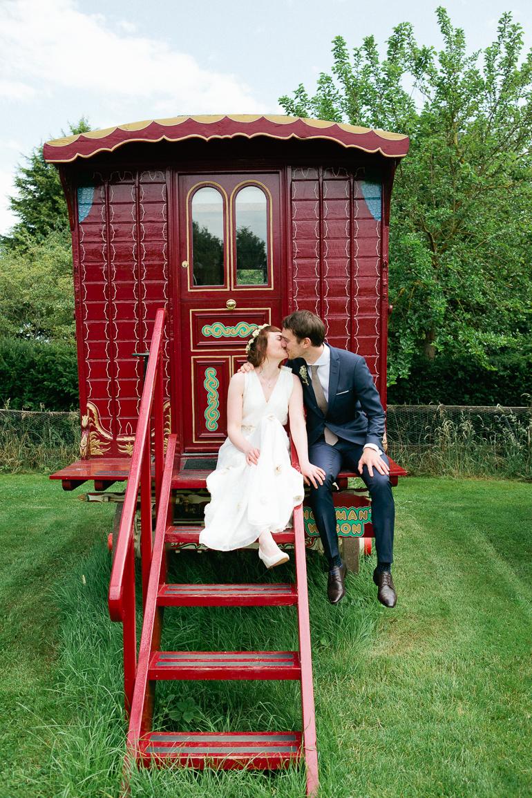 Bride and groom sit on a gypsey caravan at south farm in cambridgeshire