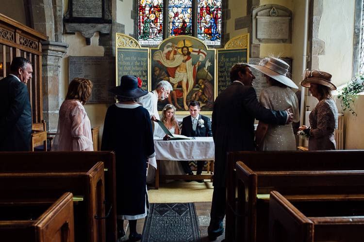The bride and groom signing the register at St Peter and St Paull Church in Wadhurts