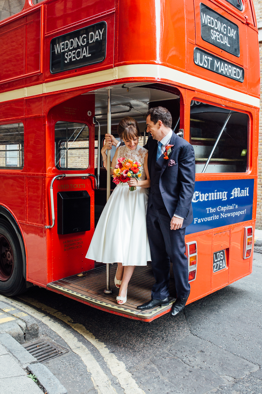 A brid and groom portrait on a red route master London Bus