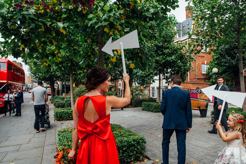A bridesmaids lead wedding guests from the a Islington Town Hall ceremony onto Red Route Master London Buses