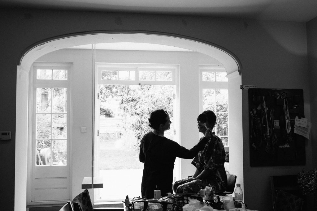 A black and white photograph of a bride getting ready before her London wedding photographed by natural Kent wedding photographer Matilda Delves