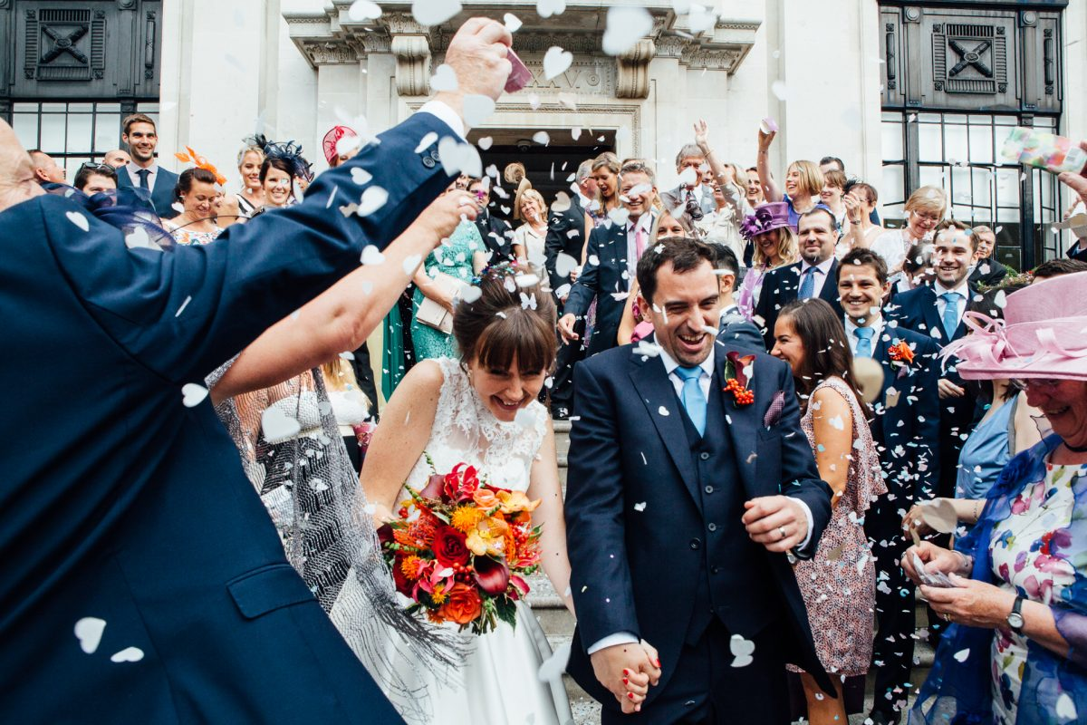 Guests throw confetti over the bride and groom at a at Islington Town Hall London wedding, photographed by natural Kent wedding photographed Matilda Delves