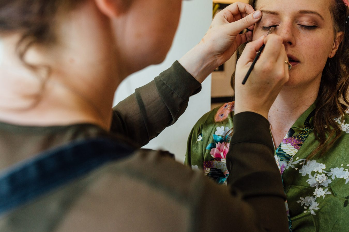 A bride has her make up put on before her London wedding photographed by natural Kent wedding photographer Matilda Delves