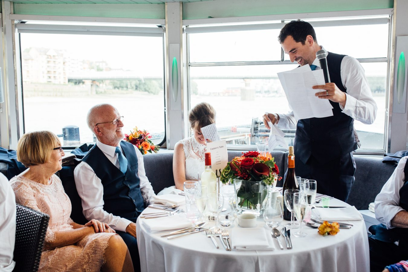 The bride and groom durring the speeches at a wedding reception on board the Erasmus luxury Thame by Kent wedding photographer Matilda Delves