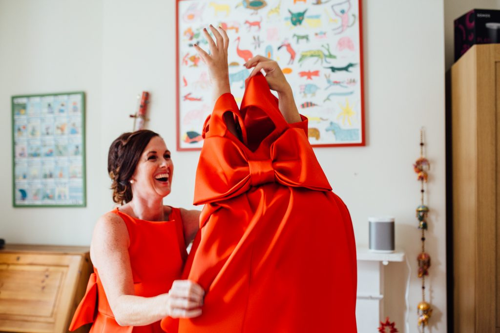 A bridesmaid puts on a bright red dress before a London wedding, photographed by natural Kent wedding photographed Matilda Delves