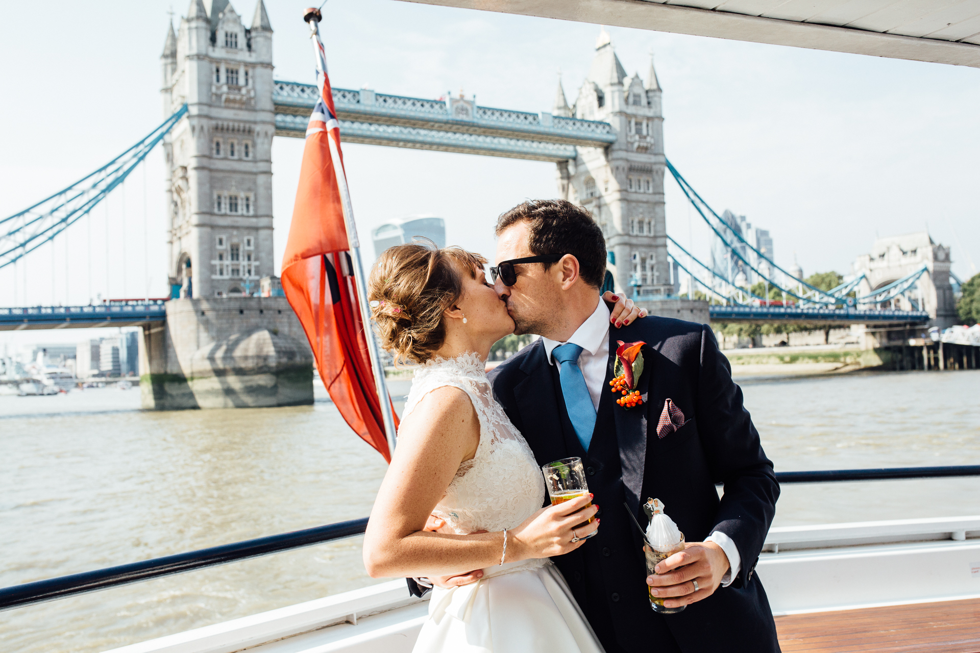 A bride and groom kissing with Tower Bridge in the background, on board the Erasmus luxury Thames by Kent wedding photographer Matilda Delves