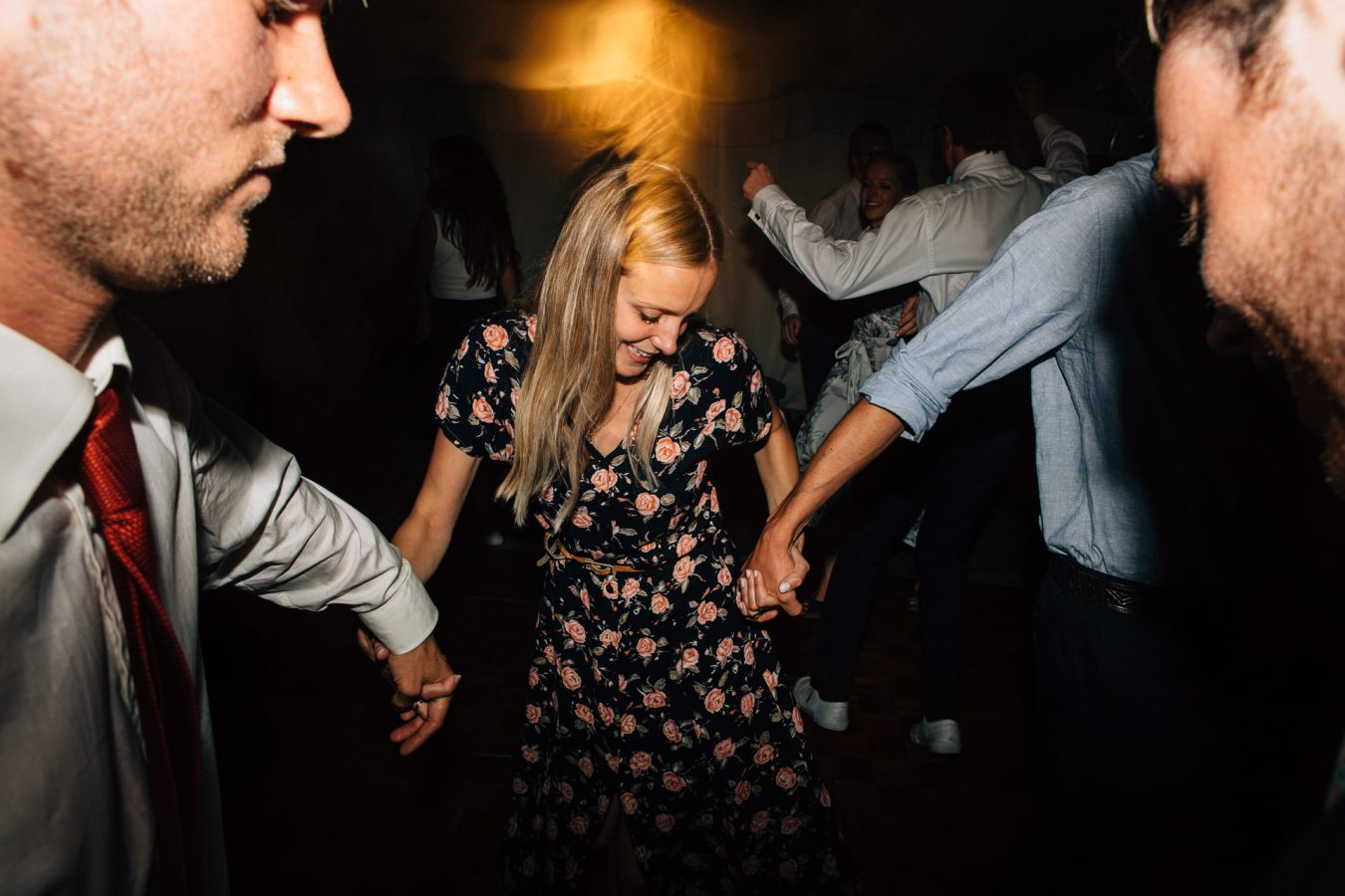 A young woman wedding guest dances into the night during a beautiful marquee wedding reception in Kent photographed by natural Kent Wedding photographer Matilda Delves