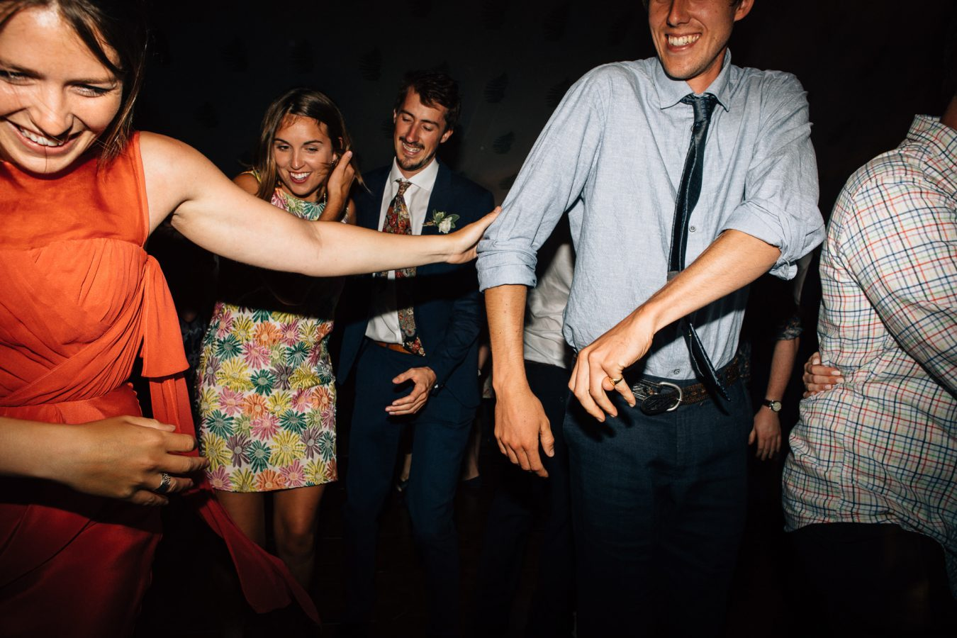 Wedding guest push each other away on the dance floor during a beautiful marquee wedding reception in Kent photographed by natural Kent Wedding photographer Matilda Delves