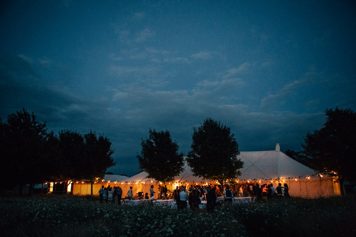 The prettiest view across a flower meadow to a beautiful House of Hud marquee wedding reception in the evening lit up my festoon lighting photographed by natural Kent Wedding photographer Matilda Delves