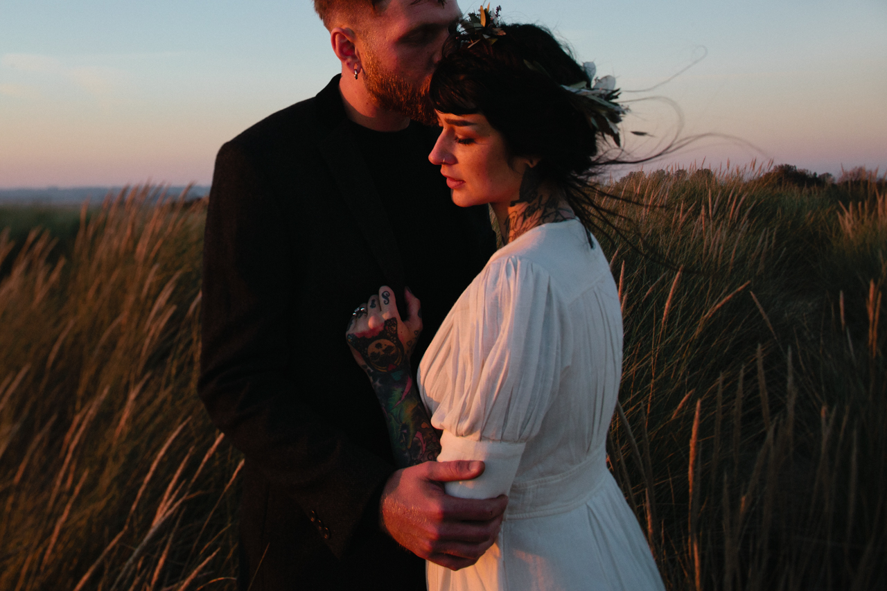 A portrait of a bride and groom at sunset in the dunes at Camber Sands by Kent and London alternative wedding photographer