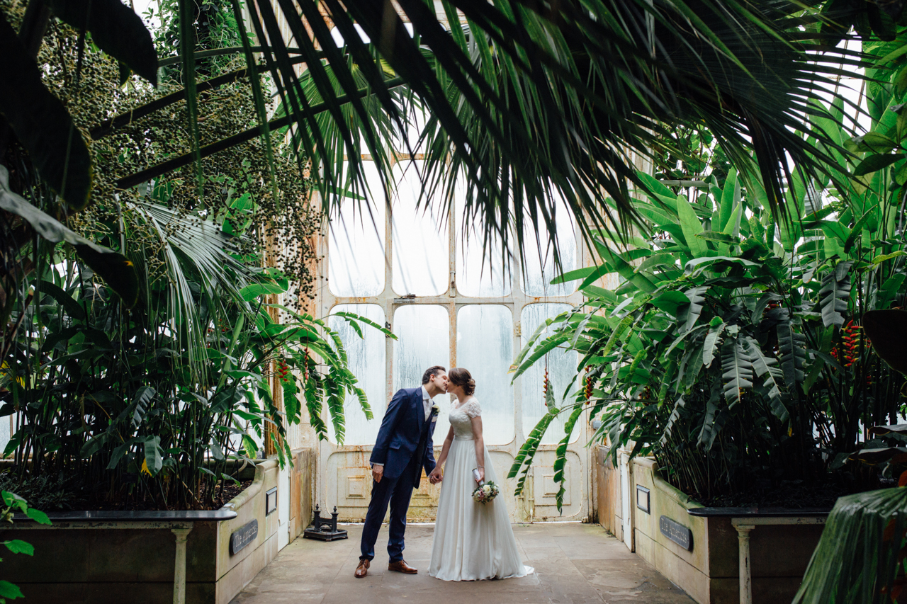 A portrait of a bride and groom kissing in the Palm House at Kew Gardens