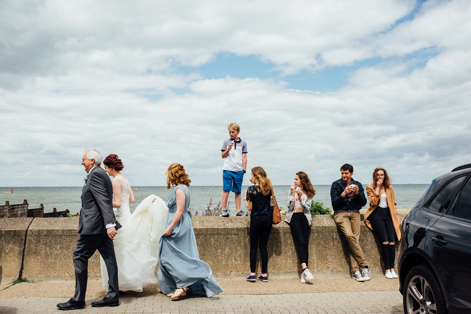 A fun portrait of a bride walking to her East Quay wedding in Whitstable by natural style Kent Wedding photographer Matilda Delves