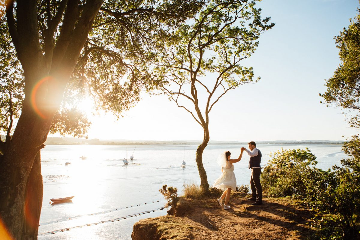 A bride and groom dance on a cliff in Devon after their ceremony photographed by natural style Kent Wedding Photographer Matilda Delves