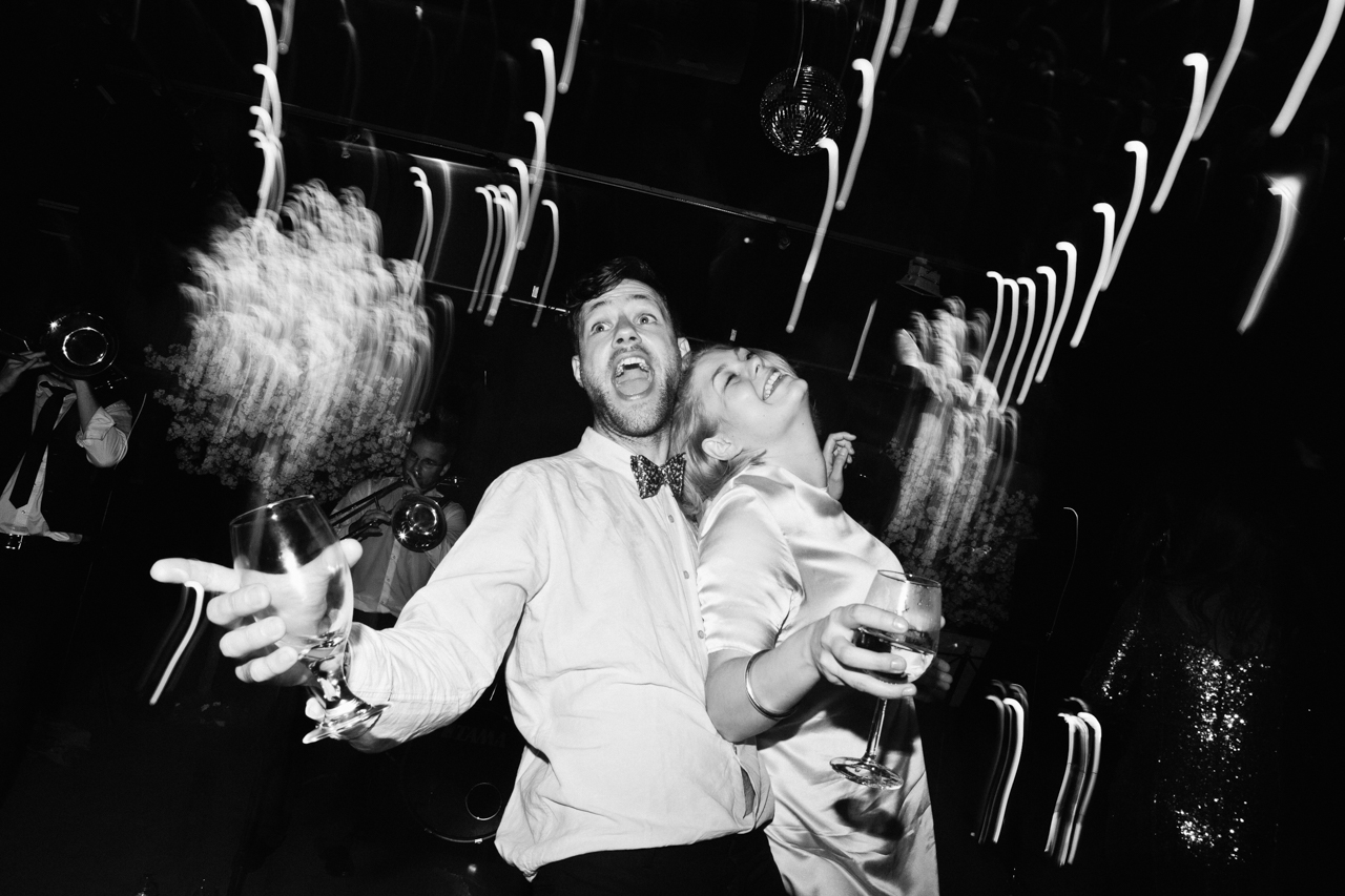 Black and white photo of two wedding guests dancing at a London wedding
