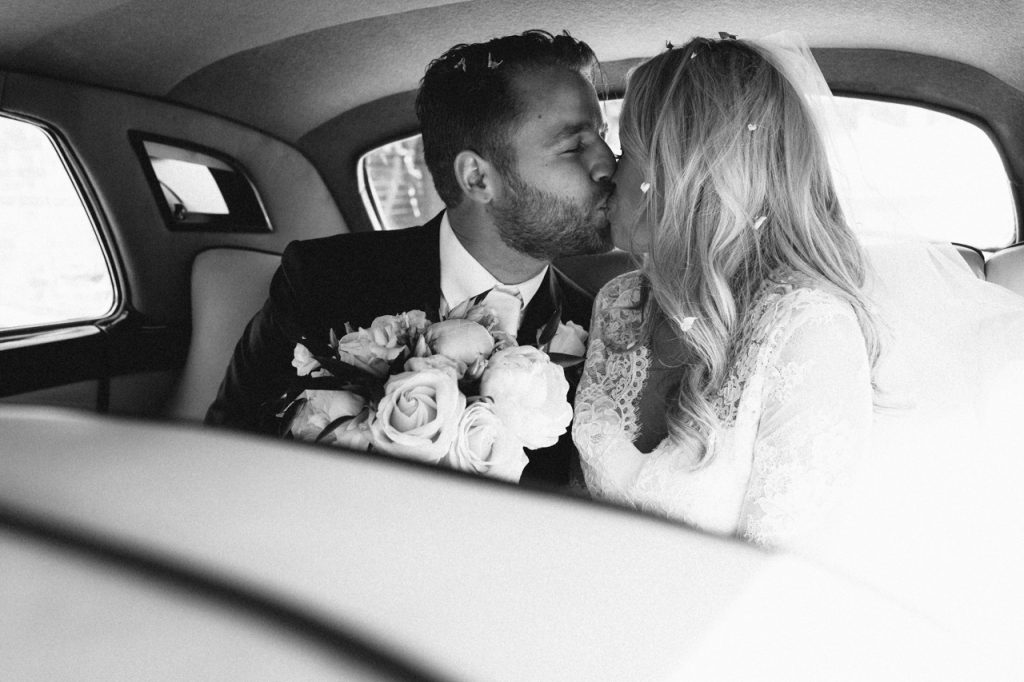 A black and white photography of a bride and groom kissing in the back of a vintage car