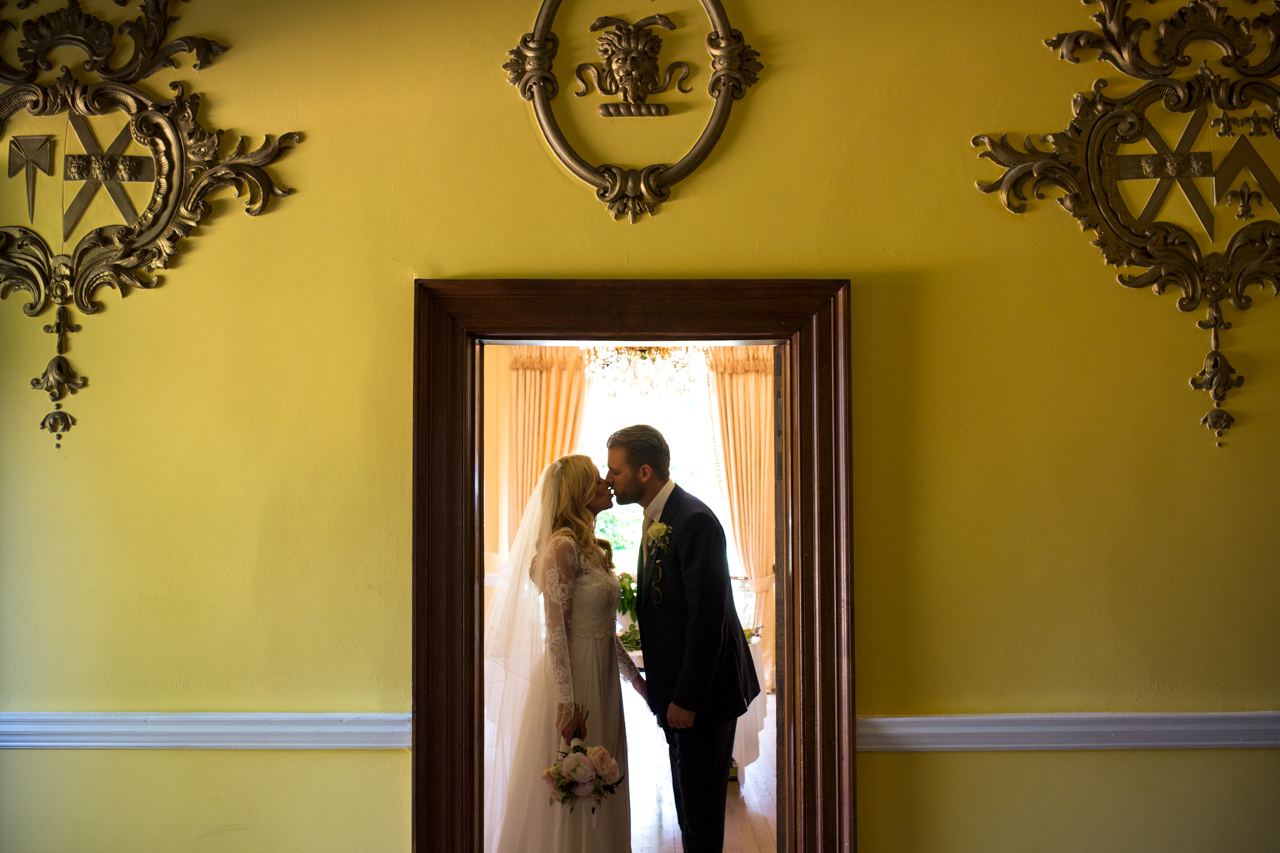 A bride and groom kissing in the yellow coloured hallway at Sprivers Mansion