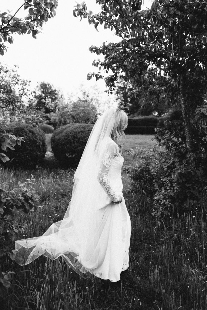 A black and white coloured photograph of a bride wearing a Charlie Brear wedding dress at Sprivers Mansion