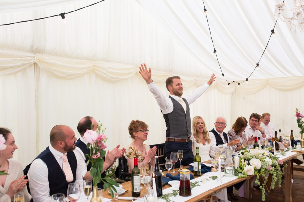 A groom holds his arms up in the air at his wedding reception at Sprivers Mansion