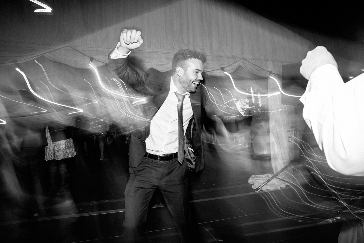 A black and white photography of a wedding guest dancing at Sprivers Mansion