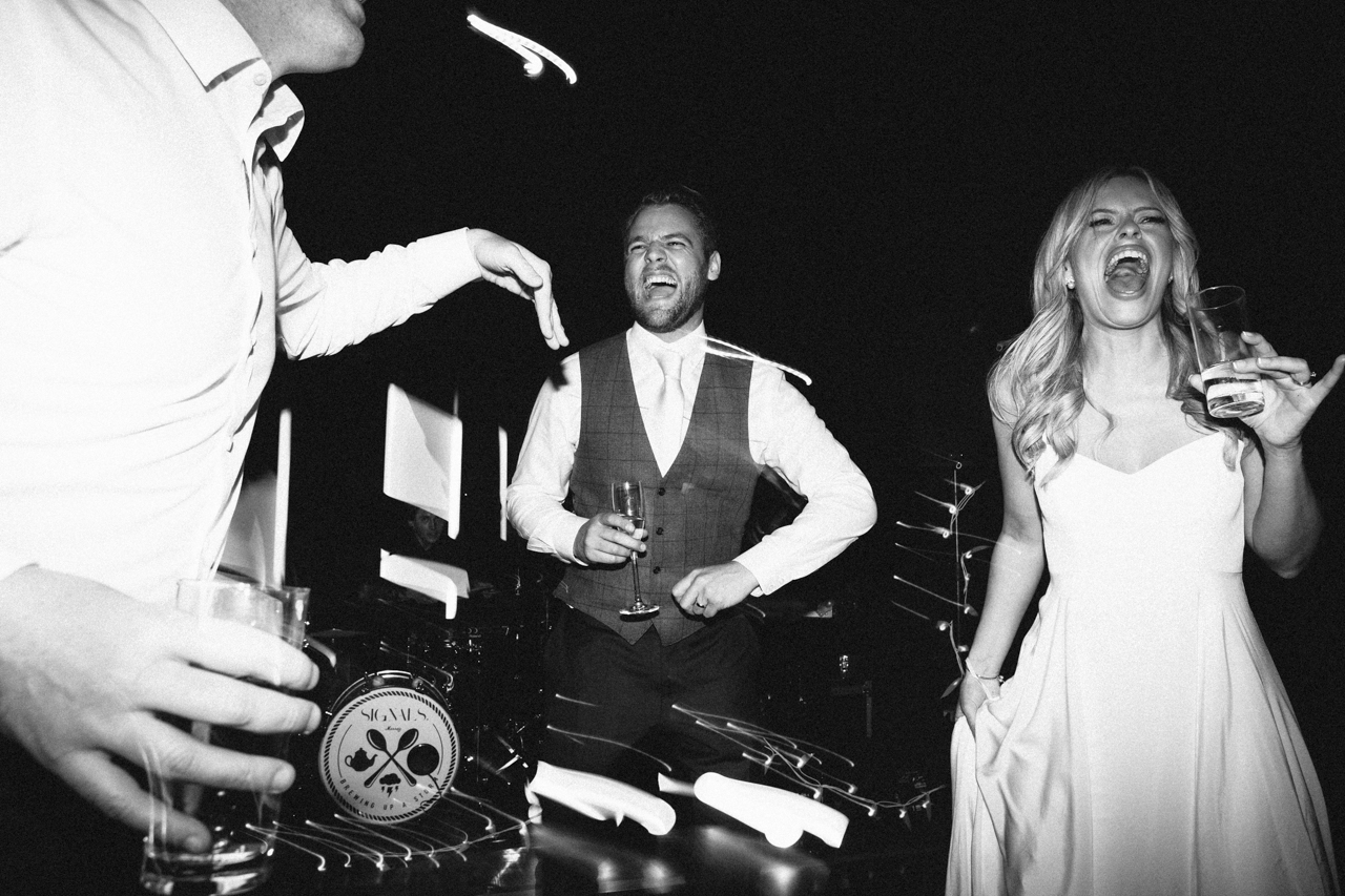 A black and white photography of a bride and groom dancing to wedding band The Signals