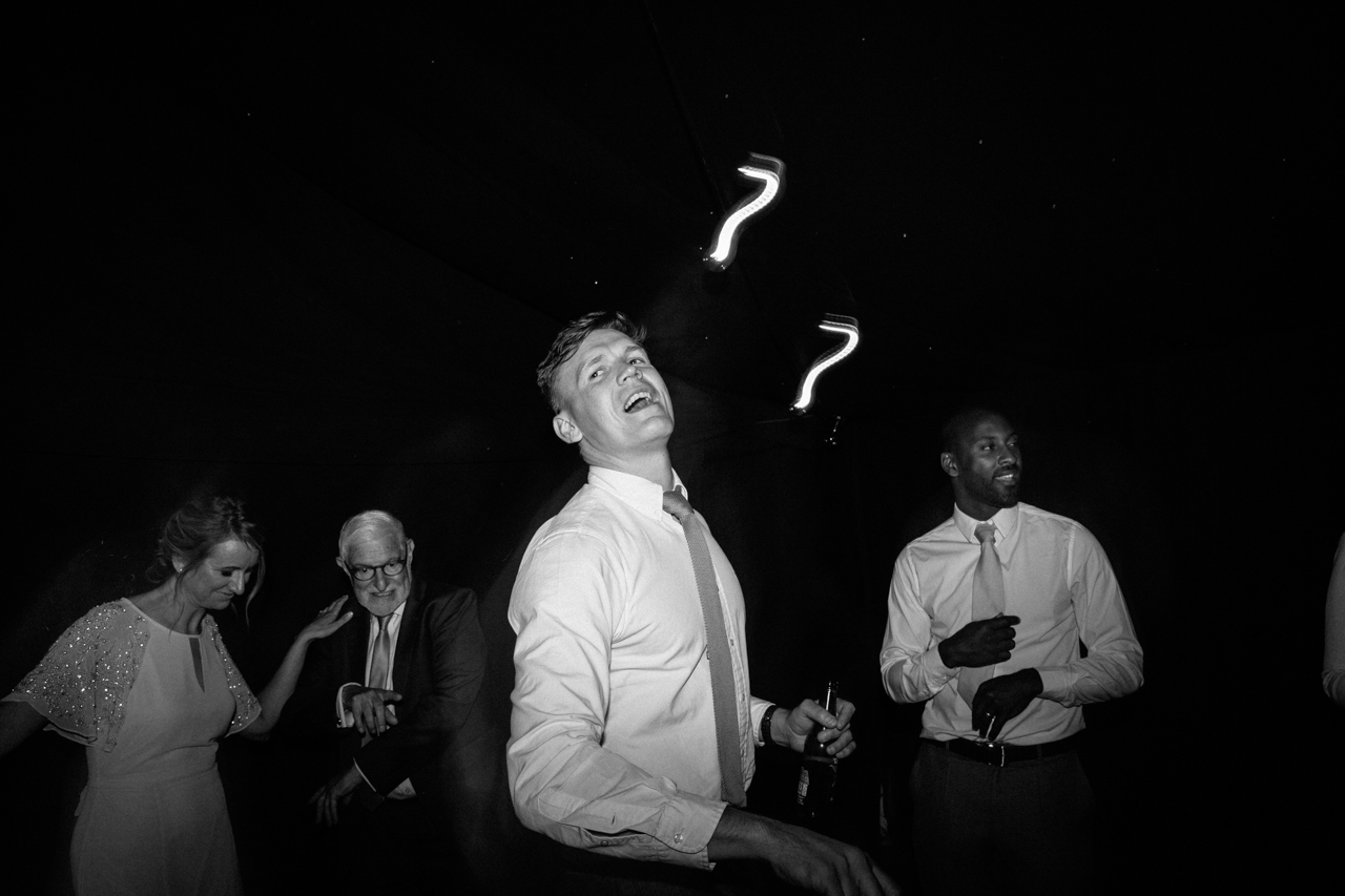 A black and white photography of wedding guests daning the weddign band The Signals