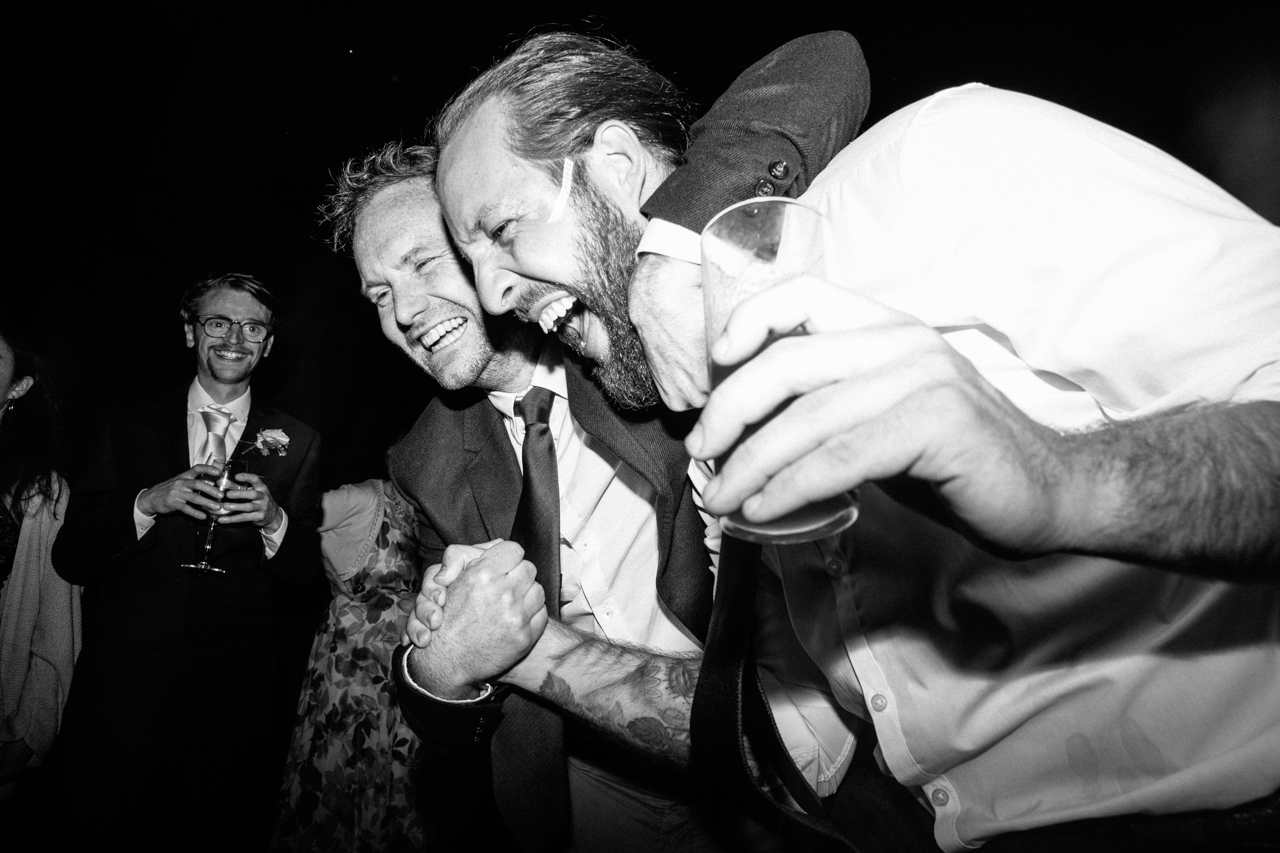 A black and white photography of drunk wedding guests dancing at Sprivers Mansion -Kent documentary weddign photography
