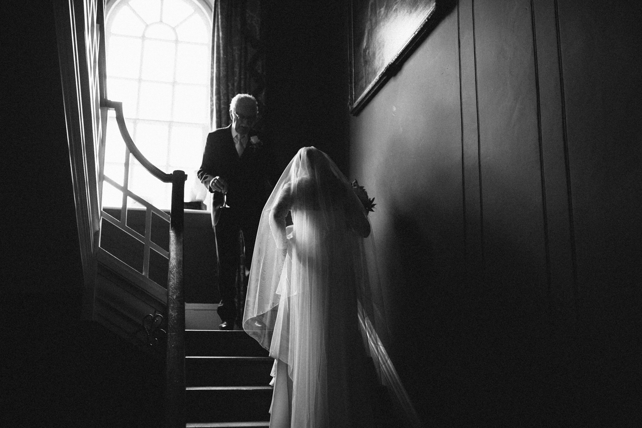 A black and white photo of a bride meeting her father on the stairs in Sprivers mansion