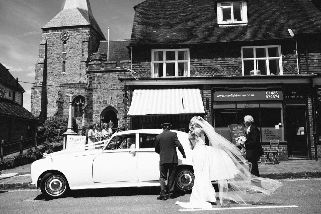 A black and white photography of a bride getting out of the car at Mayfield Church
